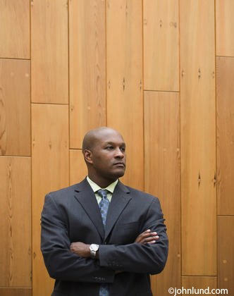 A handsome bald black businessman wearing a sharp looking suit is waiting for an appointment. He is standing with his arms crossed in front of him and has a serious look on his face. The man is standing against a wood paneled wall.